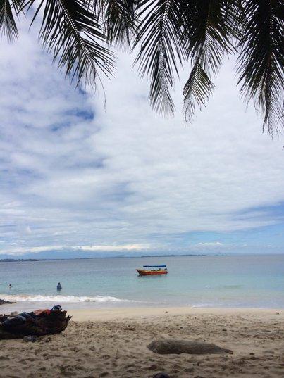 Малка лодка, гледана от пясъчен бряг.