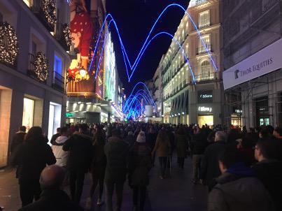 Много хора на улица под коледна украса