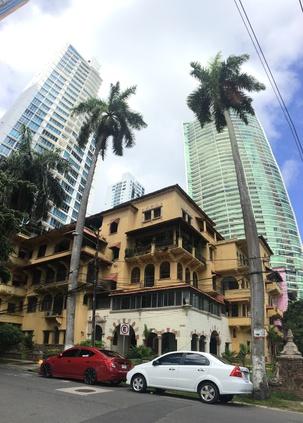Малка сграда и две палми на фона на два небостъргача